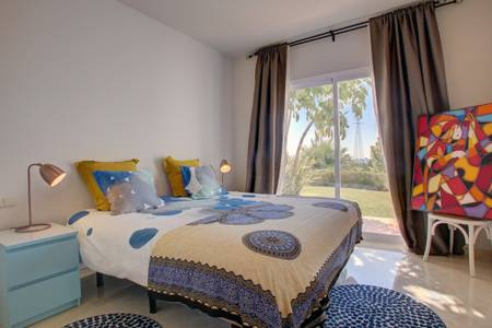 Image shows large king size bed and large windows that walk onto terrace and garden