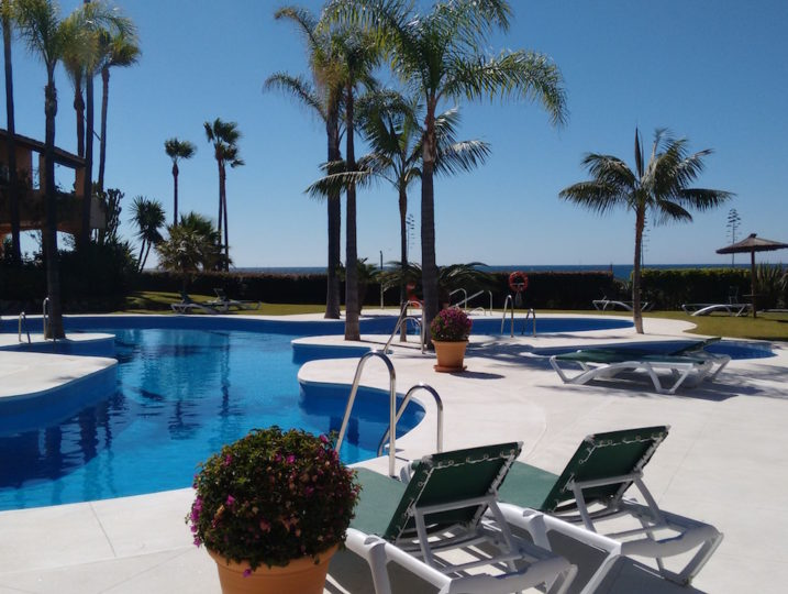 Holiday Rentals Estepona Image shows the shared pool facility along with some sund beds.