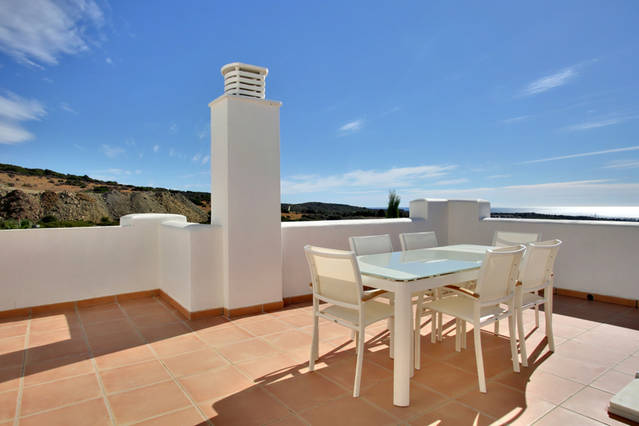Image shows table and 6 chairs and views of blue sky and mediterranean sea