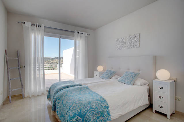 Image shows large double bed and turquoise decor