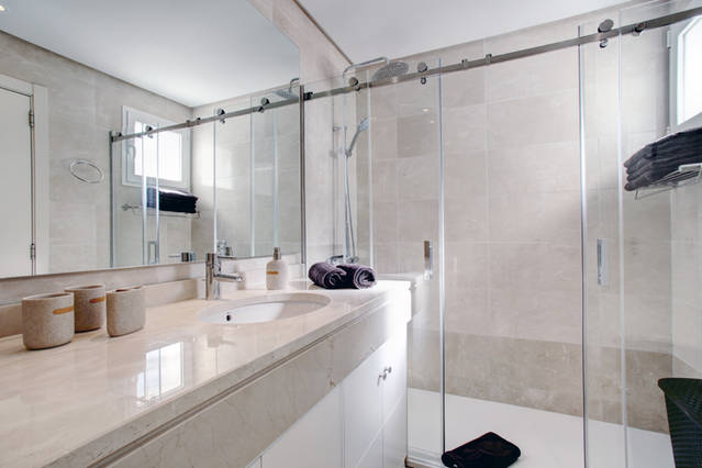 Image shows large walk in shower and a double sink basin