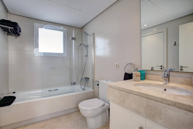 Image shows large marble bathroom with bathtub & shower