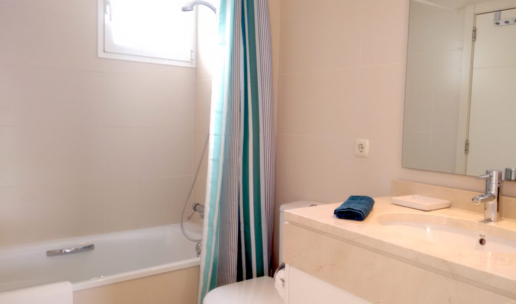 Image shows marbel bathroom with bath tub and shower