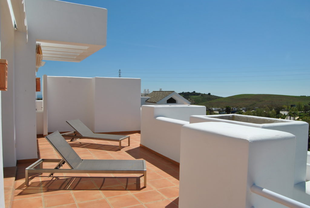 Image shows large terrace with sunloungers