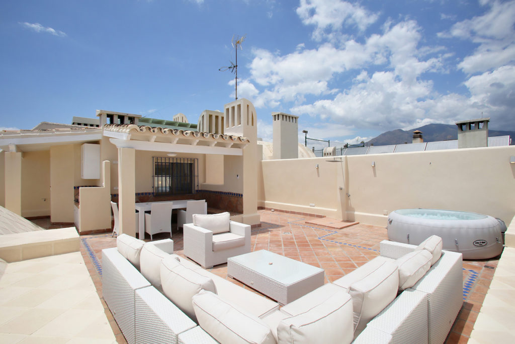 Image shows panoramic view of the private roof terrace along with hot tub, lounge furniture and dining table/chairs.