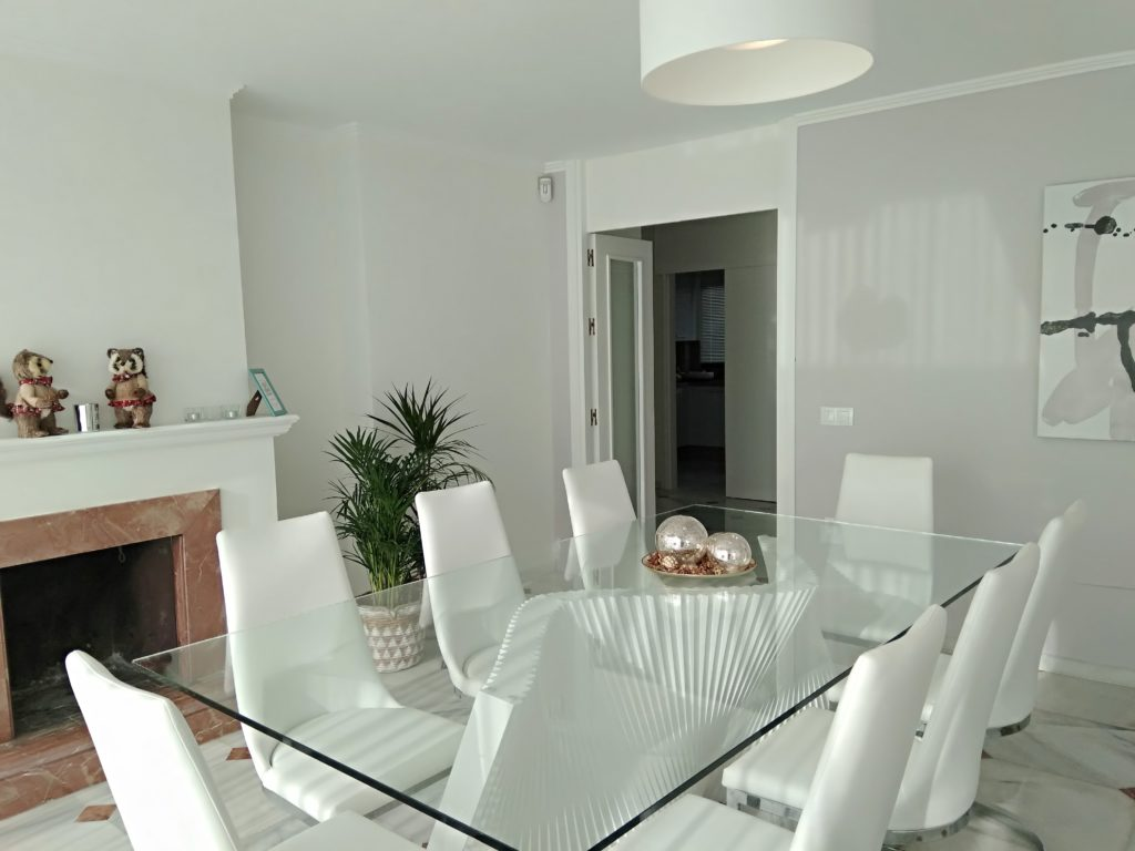 Image shows close up of dining area with glass table and six chairs