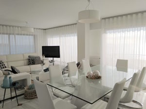 Luxury beachfront penthouse in Estepona. Image shows dining area in foreground and lounge area at rear with curtains over all windors/patio doors to terrace.