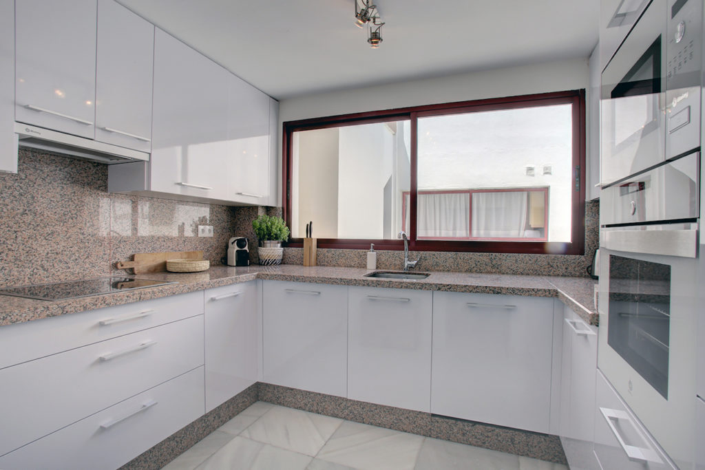 Images show the kitchen with tiled walls and floor and range of modern units.
