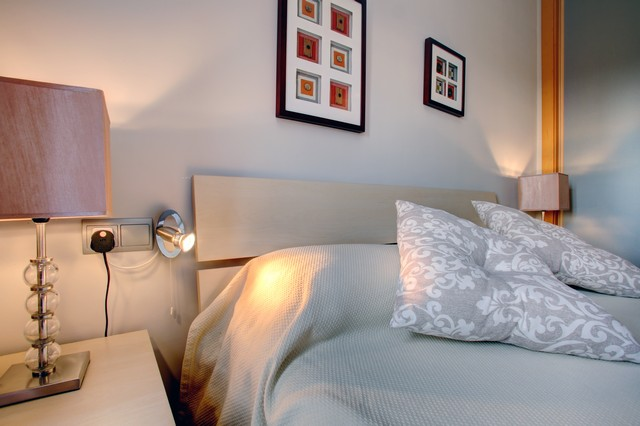 Image shows close up of bed in third bedroom with cushions in addition to pillows and wall mounted reading lamps
