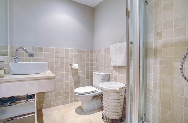 Image shows third bathroom with white suite and walk in shower unti.