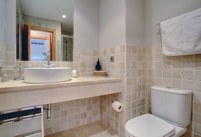 Image shows the bath of the main bathroom and this area has fully tiled walls.