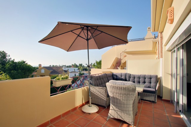Image shows the balcony/terrace with lounge furniture and sun shade