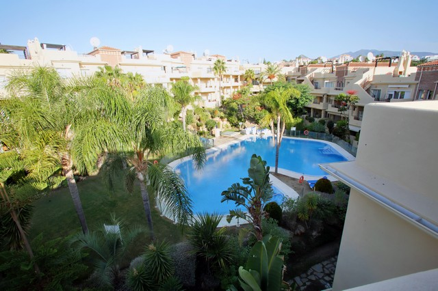 Estepona Holiday Rentals Apartments - Toscana Hills: TH1211. Image shows the view from the terrace to the pool that belongs to the complex