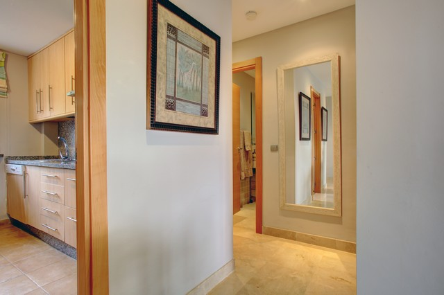 Images shows hallway with large wall mirror and entrance to kitchen