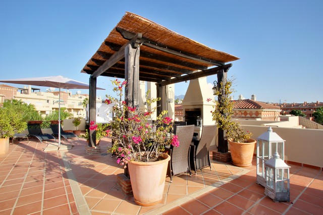 Estepona Holiday Rentals Penthouses - Toscana Hills: TH1221. Image shows wide angle view of the overall roof terrace with the covered dining area and the BBQ in the centre of the image