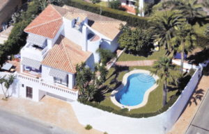 Image shows aerial view of villa with pool and gardens to the right, the main villa in the centre - not the small terrace overooking teh pool - and the al fresco dining to the left.