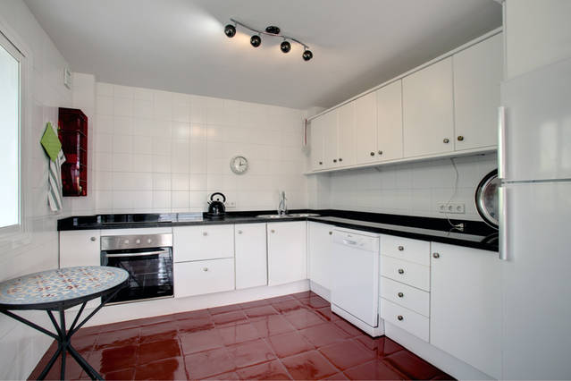 Image shows kitchen with tiles floor and walls and range of modern base and wall units.