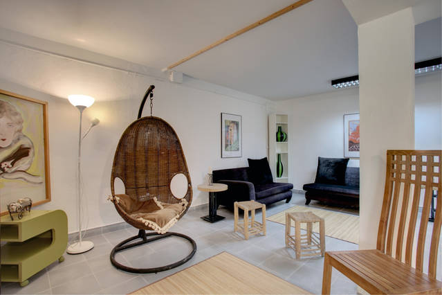 "Image shows the basement ""chill out"" area with suspended wicker chair and lounge furniture"