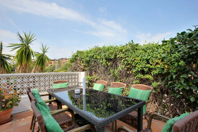 IMage show table and chairs on terrace in mature garden area