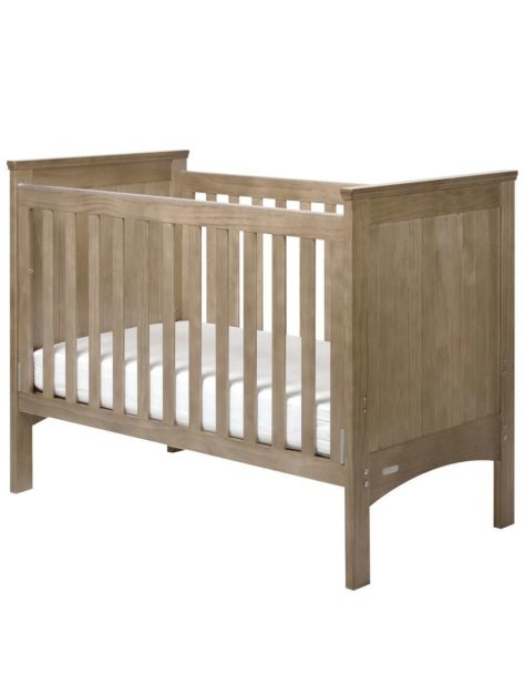 Image show a standard infants cot with wooden slats.