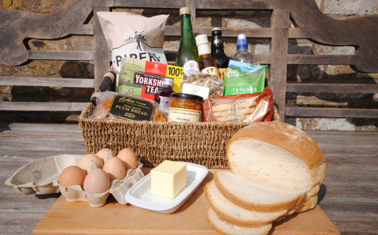 Image shows a wicker hamper with groceries therein.