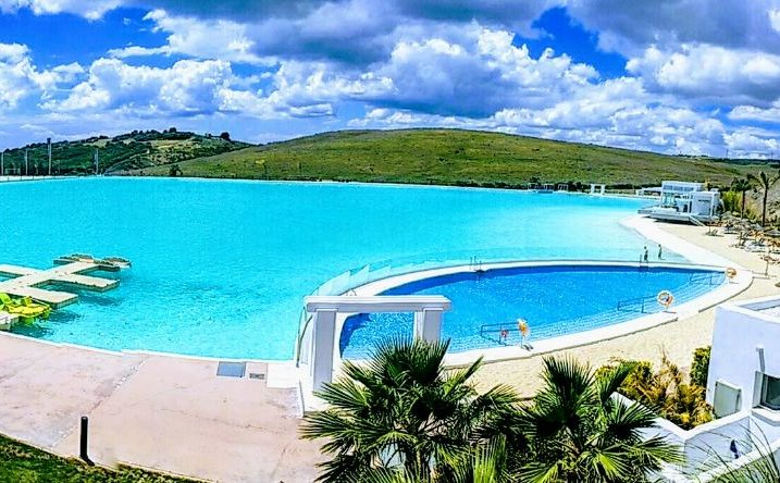 Image shows panoramic view of the crystal lagoon and blue skies