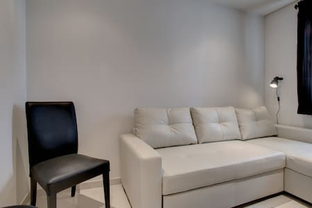 Image shows thirs bedroom with large white leather sofa bed