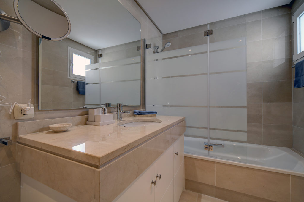 Image shows large bathroom with a bath tub ad marble counters