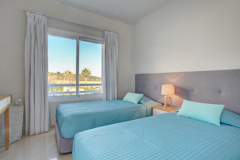 Image shows twin beds and a window with views to mountains
