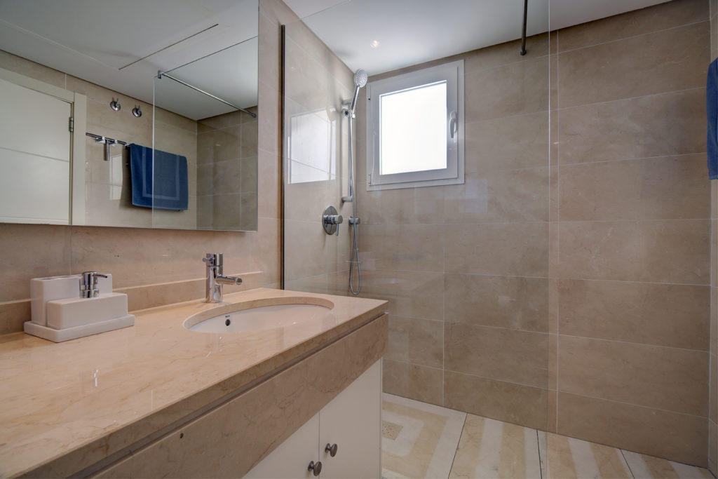 Image shows large marble bathroom with a walk in shower