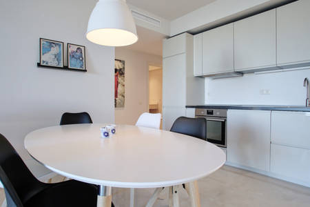Image shows table and chairs and kitchen in background