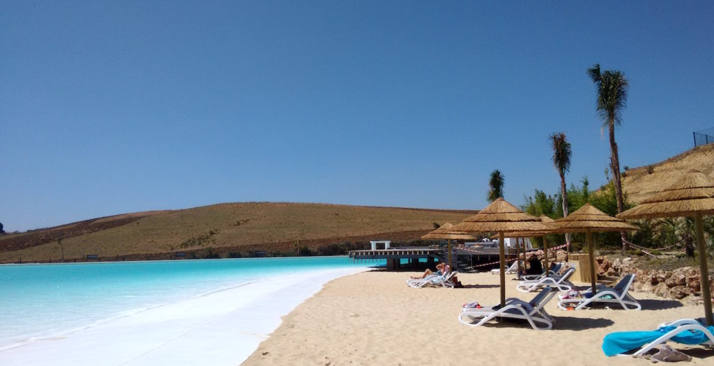 Image shows crystal lagoon with white sand and sunloungers and umbrellas