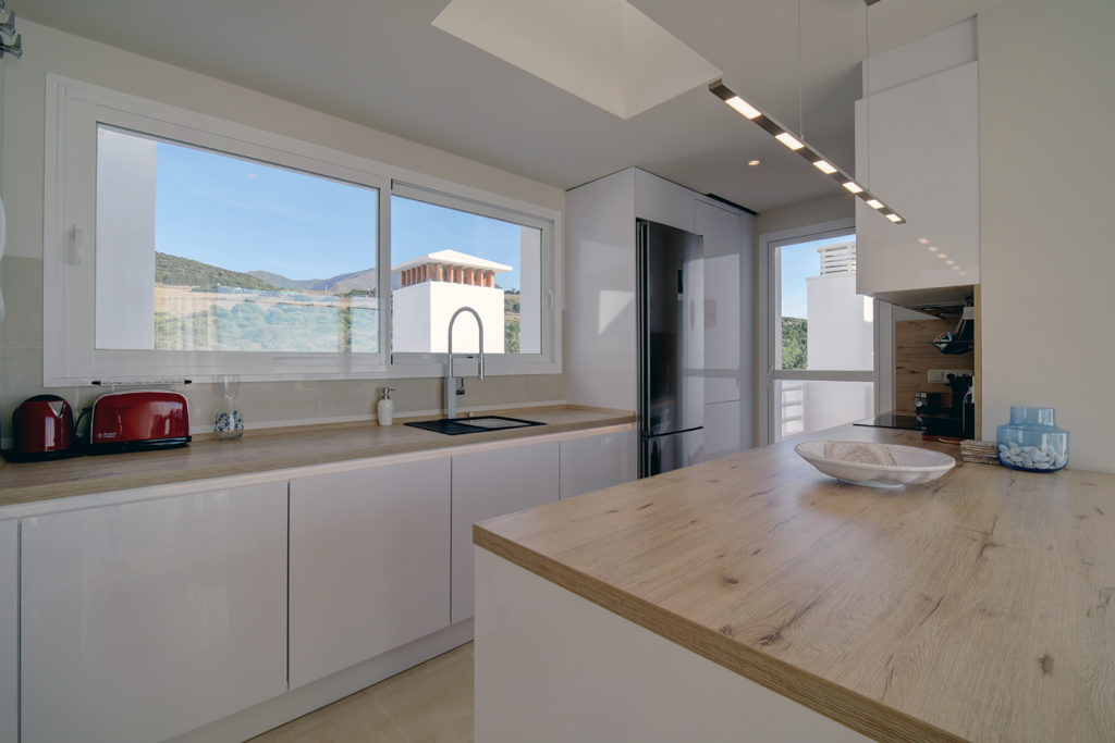 Image shows open kitchen space with window and views to mountains