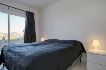 Image shows large bed with view onto terrace & gardens