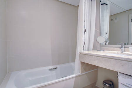 Image shows marble bathroom with dual sinks and bathtub