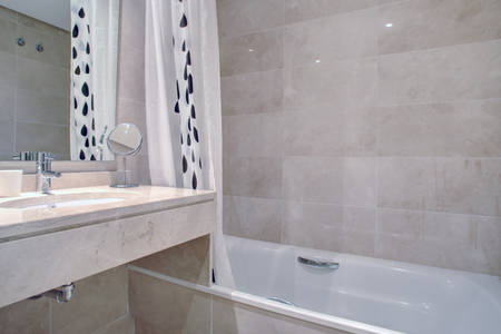 Image shows large marble bathroom with bath tub & shower