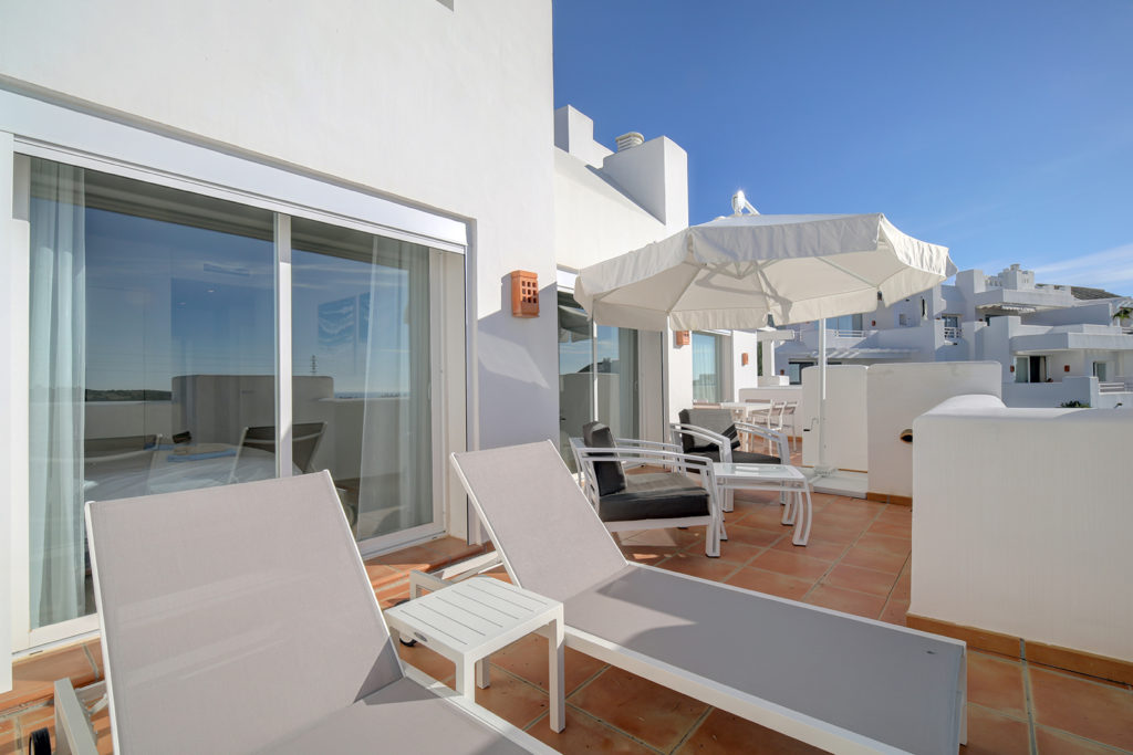 Image shows terrace with 2 sunbeds and dinnig table