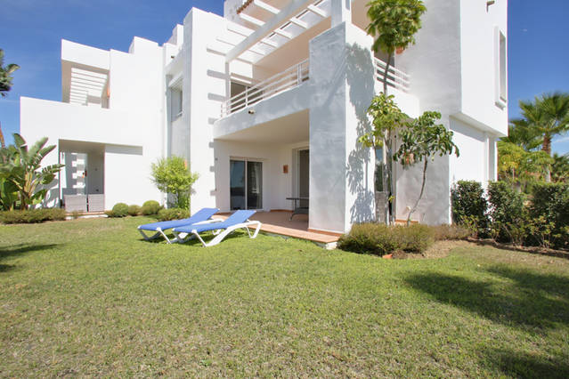 Imae shows terrace with sun loungers and tropical gardens