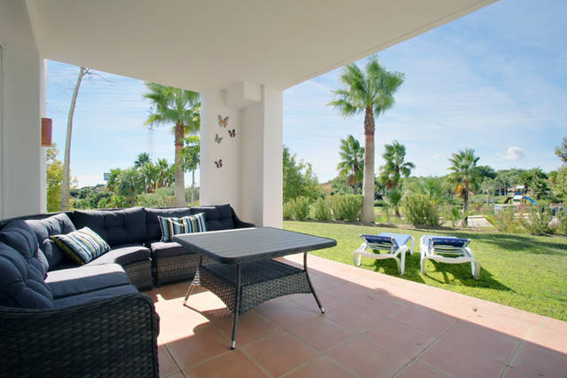 Image shows outside seating are and view to the Alcazaba Lagoon resort and manicured gardens