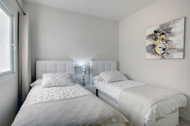 Image shows 2 twin beds and ultra modern furniture