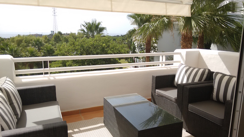 Image shows terace looking out to sea and Lagoon , with sofas and sunshades