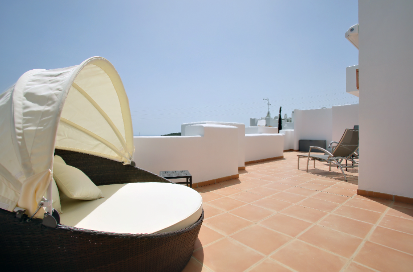 Image shows large sunlounger on large terrace
