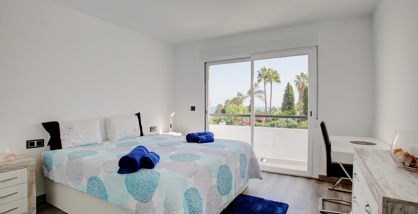 Estepona Holiday Rentals Townhouses - Bahia Doncella. Image shows a king size bed, a big terrace and views to the mediterranean sea