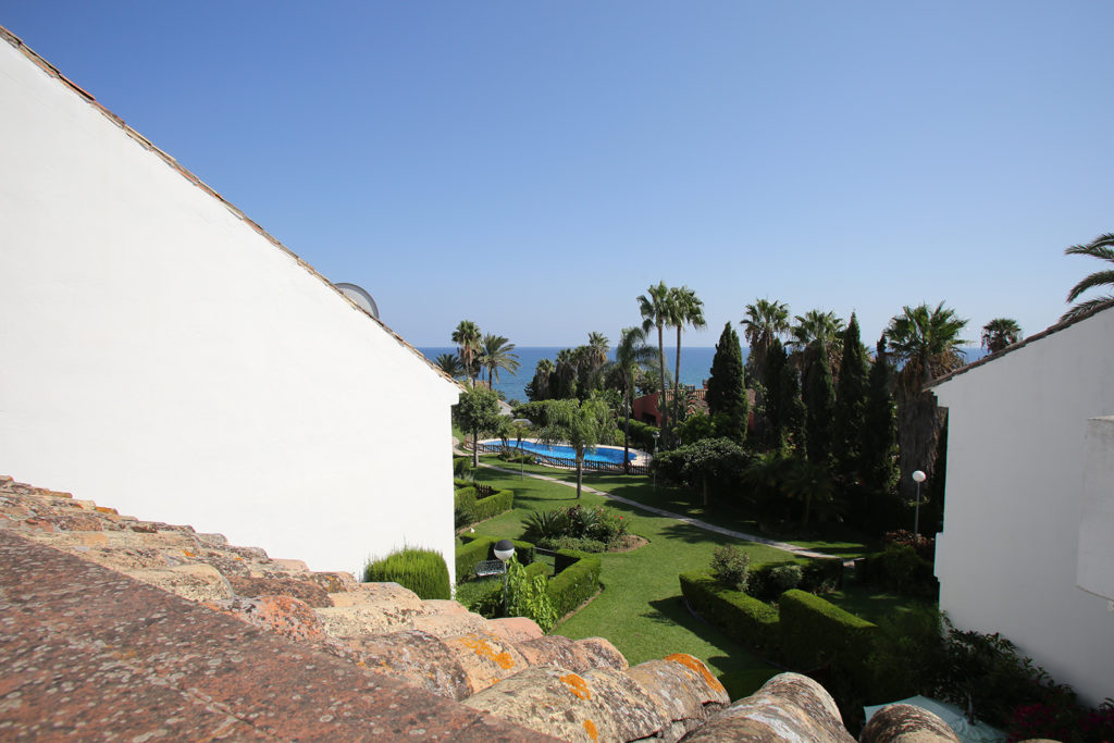 Image shows a sea view and tropical gardens and swiming pool