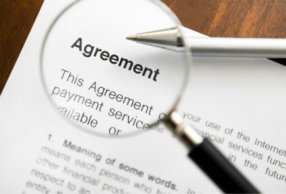 The image shows a typical agreement with a magnfying glass oveer those words.