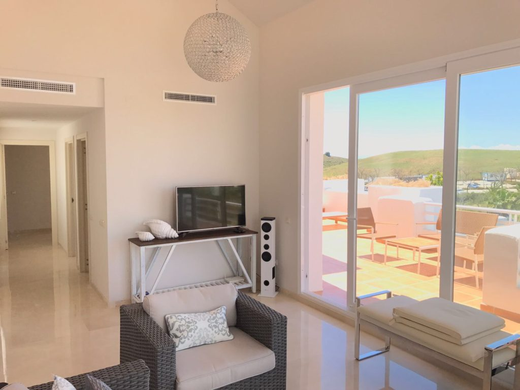 Image shows alternate view of the lounge and across onto the terrace of this stylish penthouse in Alcazaba Lagoon