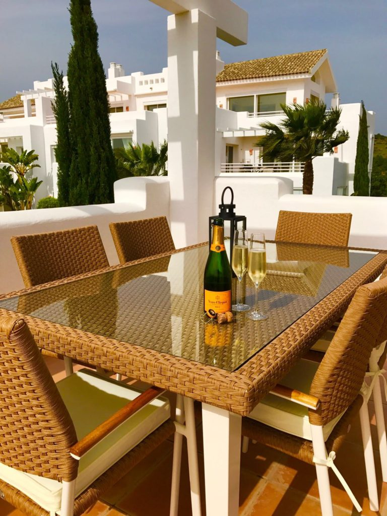 Image shows table and chairs on outside terrace of this stylish penthouse in Alcazaba Lagoon