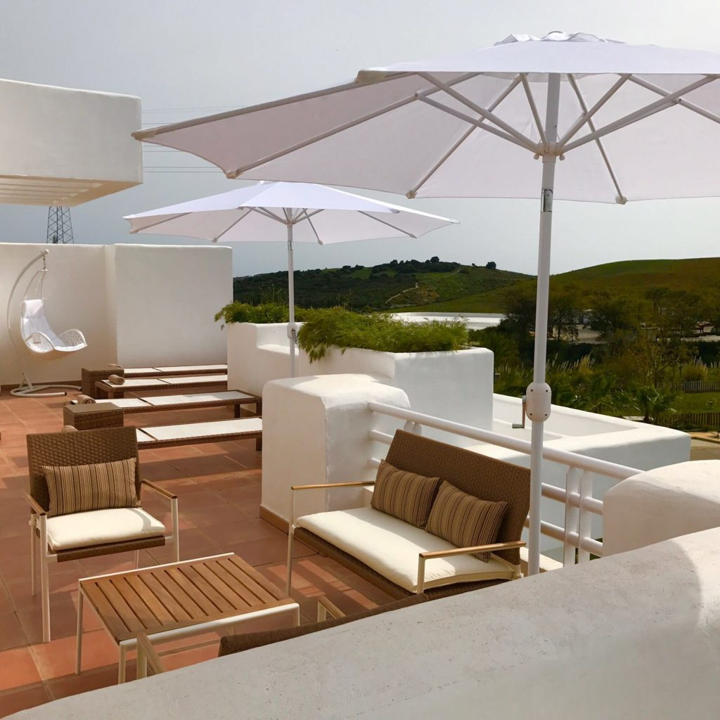 Image shows the terrace including table, chairs and sunbeds of this stylish penthouse in Alcazaba Lagoon