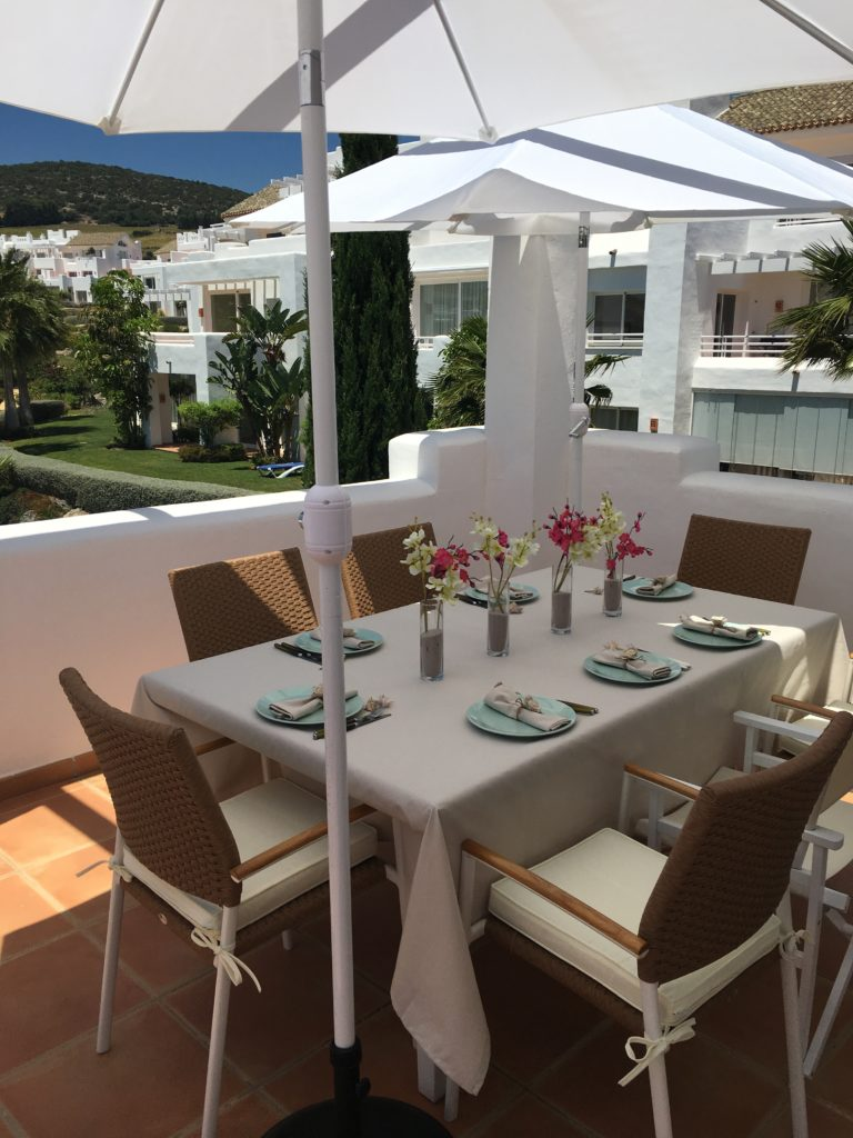 Image shows the dining table on the terrace of this stylish penthouse in Alcazaba Lagoon set for a meal