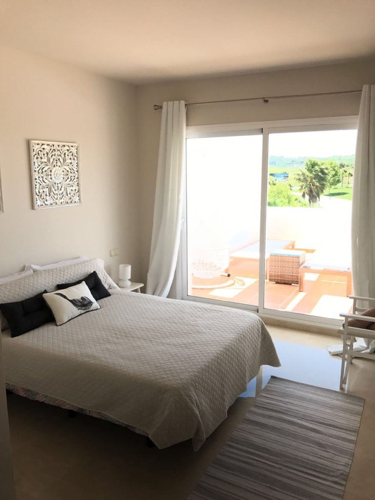 Image shows the main bedroom of this stylish penthouse in Alcazaba Lagoon with a large double bed and access to the terrace